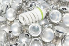 Light bulbs. Energy saving light bulb and a big number of traditional bulbs royalty free stock photos