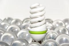 Light bulbs. Energy saving light bulb and a big number of traditional bulbs stock image