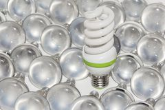 Light bulbs. Energy saving light bulb and a big number of traditional bulbs royalty free stock photo