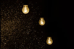 Light bulbs on a black background with sparkles Royalty Free Stock Photos