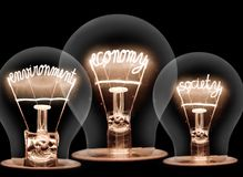 Light Bulbs Concept. Photo of light bulbs with shining fibres in ECONOMY, ENVIRONMENT and SOCIETY shape on black background; concept of SUSTAINABILITY royalty free stock photography