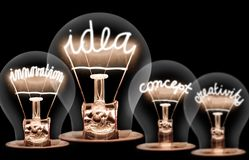 Light Bulbs Concept. Photo of light bulbs with shining fibres in IDEA, VISION, CONCEPT and CREATIVITY shape on black background stock photo