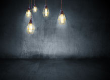 Light bulbs in concrete room Stock Photo