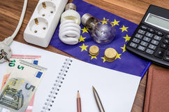 Light Bulbs on european banknotes with empty notepad and pen, calculator Stock Image