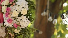 Light bulbs garland and flowers composition. Electric lamps hanging on tree as decoration for holiday close up rack. Light bulbs garland and wedding flowers stock video footage