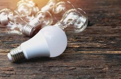 Light bulbs with glowing on wooden table background. Idea, creativity and saving energy with light bulbs concept. stock image