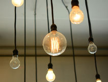 Light Bulbs hanging on the ceiling. Some on and some off Royalty Free Stock Photo