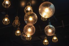 Light bulbs hanging, interior design. Many vintage light bulbs hanging by wire. Interior house and restaurant decoration design with copy space for text Stock Photo