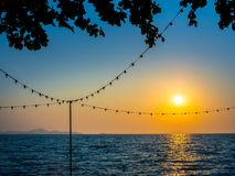 Light bulbs hanging on string wire and.the sun on sunset sky. And seascape background stock photos