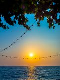 Light bulbs hanging on string wire and.the sun on sunset sky. And seascape background vertical style royalty free stock photography