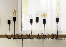 Upside down light bulbs interior design. Light Bulbs hanging from a wooden cross-beam, upside-down photography stock images