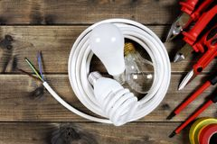 Top view of work tools and electrical system components on antique wooden background. Light bulbs inside a white roll of electric cable and work tools on an royalty free stock photo