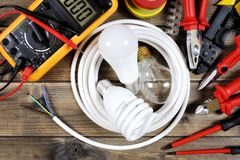 Top view of work tools and electrical system components on antique wooden background. Light bulbs inside a white roll of electric cable and work tools on an stock images