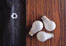 Light Bulbs Mimic Recycling Triangle. Light bulbs on wood table mimic recycling triangle Royalty Free Stock Photos