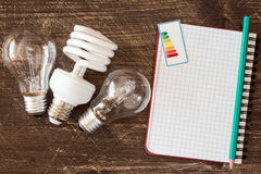 Light bulbs and notebook with energy efficiency label Stock Image