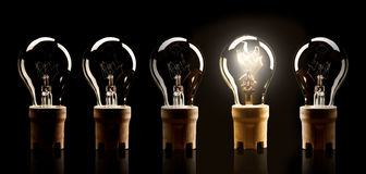 Light bulbs in row with single one shinning Stock Image