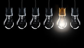 Light bulbs in row with single one shinning Royalty Free Stock Image