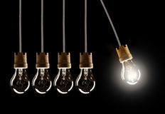 Light bulbs in row with single one shinning Stock Photography