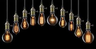 Light bulbs. Set of vintage glowing light bulbs on black Stock Image