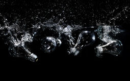 Light bulbs splashing in water. Light bulbs falling in water with a splash on black background royalty free stock photos