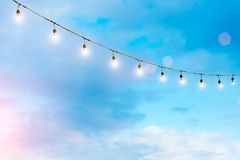 Light bulbs on string wire against the sky. Party light. Good li Stock Image