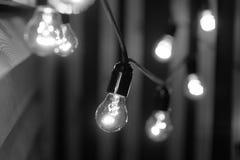 Black and white light bulbs. Light bulbs on wooden background. Christmas lights Royalty Free Stock Photos