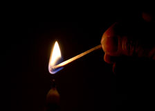 Light a Candle. Fingers lighting a candle with a matchstick in the dark Stock Photo