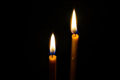 Light candle. Light and bright golden yellow candle amidst darkness Royalty Free Stock Photo
