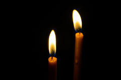 Light candle. Light and bright golden yellow candle amidst darkness Stock Photo