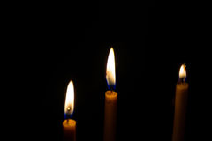 Light candle. Light and bright golden yellow candle amidst darkness Royalty Free Stock Images