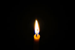 Light candle. Light and bright golden yellow candle amidst darkness Stock Photography