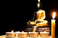 Light candle with Buddha statue and light dark background . Royalty Free Stock Image