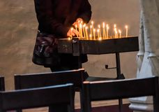 Light a candle in a Christian church to commemorate the deceased Stock Photos