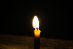 Light candle. Light and bright golden yellow candle amidst darkness Royalty Free Stock Photography