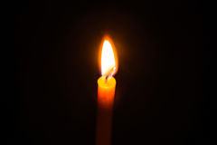 Light candle. Light and bright golden yellow candle amidst darkness Stock Photos