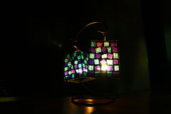 Light a candle in the mirror. The lamp of colored glass with a candle in the mirror royalty free stock image