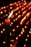 Light candles in a crypt. Hundreds of candles glow in a dark crypt stock image