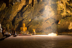 Light in the cave with sitting Buddha statue. Stock Images
