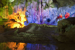 Light through the Caves. The colorful lights inside Sung Sot cave in Vietnam reflect in the waters Stock Images