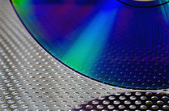 Light and CD. Closeup of CD on a perforated metal surface Royalty Free Stock Images