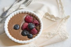 Light chocolate dessert with raspberries and blueberries on the background of an elegant napkin with frills and a vintage spoon an royalty free stock photography