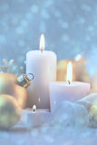Light Christmas Decorations with Candles, baubles and magic snow Stock Photo