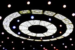 Light and circles on the ceiling with ornament glows like a UFO on a black background. White lights on a black background Stock Images