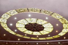 Light and circles on the ceiling with ornament glows like a UFO on a brown background. With spotlight Stock Image