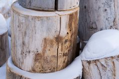 Light colored logs stacked in snow in winter. Many large light colored logs stacked in snow in winter royalty free stock images