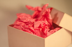Light-coloured box with pink present paper. Light-coloured opened square present box without lid with pink paper inside on the light background royalty free stock images