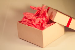 Light-coloured box with pink present paper. Light-coloured opened square present box without lid with pink paper inside on the light background stock photo
