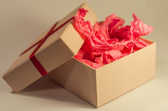 Light-coloured box with pink present paper. Light-coloured opened square present box without lid with pink paper inside on the light background stock photography