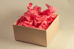 Light-coloured box with pink present paper. Light-coloured opened square present box without lid with pink paper inside on the light background royalty free stock photos