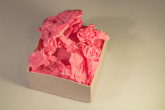 Light-coloured box with pink present paper. Light-coloured opened square present box without lid with pink paper inside on the light background stock image